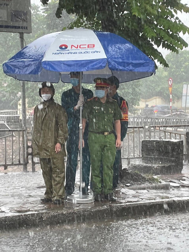 Hà Nội: Hình ảnh các cán bộ chiến sĩ làm nhiệm vụ trực chốt dưới cơn mưa tầm tã gây xúc động mạnh - Ảnh 1.