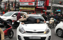 Hình ảnh người đàn ông nằm dài trên cửa kính ô tô sau va chạm giao thông vì không hoà giải được khiến nhiều người ngán ngẩm