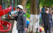 Lực lượng chức năng cầm loa ra hồ Xã Đàn, khản giọng thuyết phục người dân về nhà, không tụ tập đông người