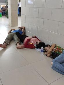 Ảnh: Nắng nóng gần 40 độ C ở Hà Nội, người nhà bệnh nhân vạ vật gần hành lang, dưới bóng cây trong bệnh viện