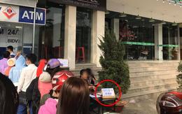 """Góc cơ hội: Người đàn ông kê bàn mở dịch vụ """"rút tiền nhanh"""" ngay cạnh cây ATM đang có hàng chục người chen chúc ngày giáp Tết"""