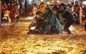 Người Sài Gòn vật lộn với đường ngập lút bánh xe, nước chảy cuồn cuộn như thác trong đêm mưa lớn