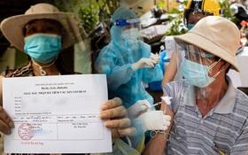 Ảnh: Người nghèo trong khu phong tỏa ở TP.HCM phấn khởi khi các đội vaccine lưu động đến tận nơi để tiêm chủng