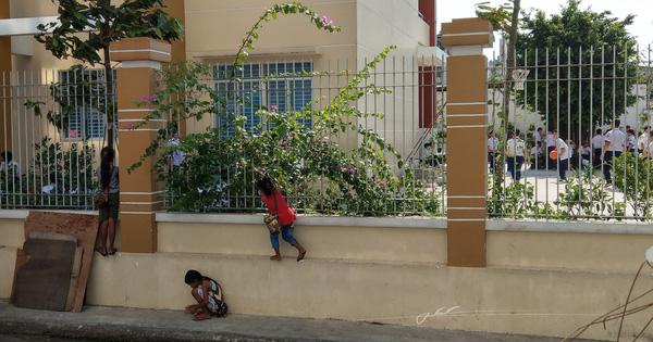 Hình ảnh 3 em nhỏ bán vé số bám hàng rào trường học để xem khai giảng gây xúc động mạnh