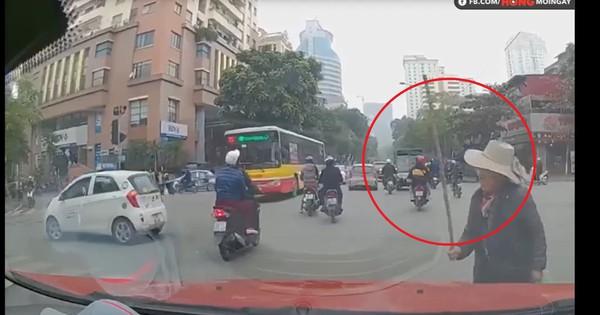 Clip: Cụ già băng phăng phăng qua đường, vừa đi vừa quơ gậy rồi đập thẳng vào kính chắn gió ô tô