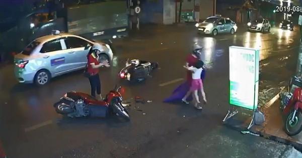 Clip: Bị tông trúng, con gái ngã bệt xuống đường do người phụ nữ dừng xe máy giữa đường để… mặc áo mưa