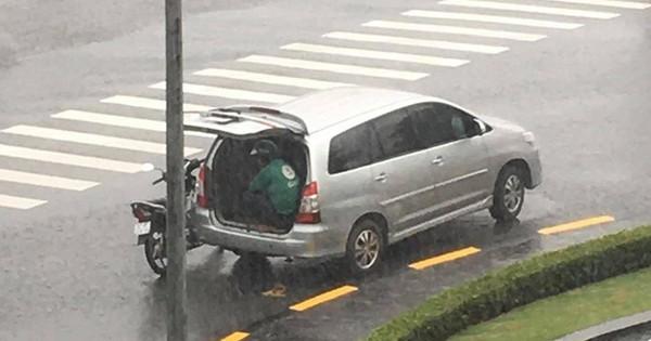 Chiếc ô tô dừng bên góc đường mở cửa cho tài xế xe ôm ngồi trú mưa, hình ảnh đẹp dưới cơn mưa lạnh khiến bao người ấm lòng