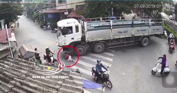 Hết hồn cảnh chiếc xe tải đang chầm chậm ôm cua thì 1 người phụ nữ chạy ra, chui dưới bánh xe để nằm