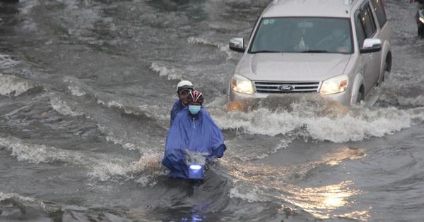 Đường phố Sài Gòn ngập lênh láng sau cơn mưa lớn, người dân khổ khổ dắt xe lội nước trên đường