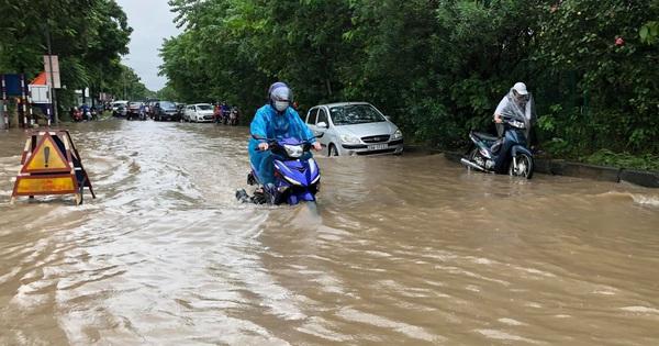 Ảnh: Mưa lớn kéo dài do ảnh hưởng của bão số 7, nhiều nơi ở Hà Nội ngập sâu, người dân chật vật di chuyển