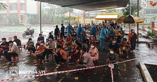 Người dân ở TP.HCM ngồi đợi dưới mưa để tiêm vaccine Vero Cell