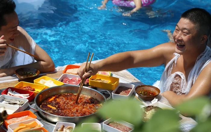 Đúng là Trung Quốc cái gì cũng nghĩ ra được: Vì thời tiết quá nóng nực, người dân rủ nhau tràn xuống bể bơi ngồi ăn lẩu siêu cay!